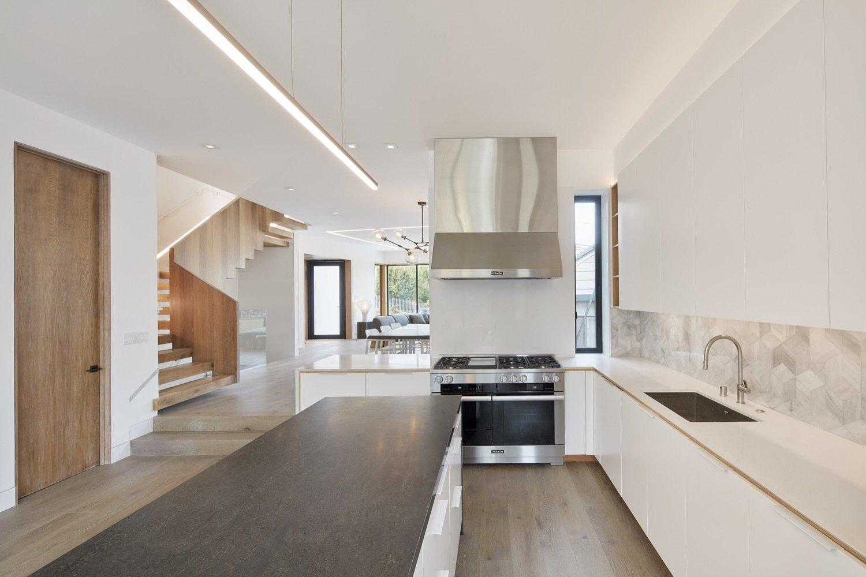 Kitchen, Engineered Quartz Counter, Wood Counter, White Cabinet, Ceramic Tile Backsplashe, Light Hardwood Floor, Track Lighting, Range, Range Hood, and Undermount Sink Kitchen  Noe Valley House