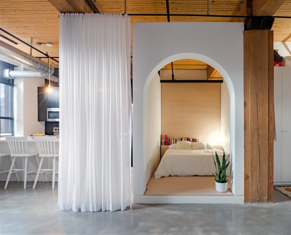 This small, L-shaped apartment by Studio AC has a bed box with an arched doorway with white walls and plywood finishings.