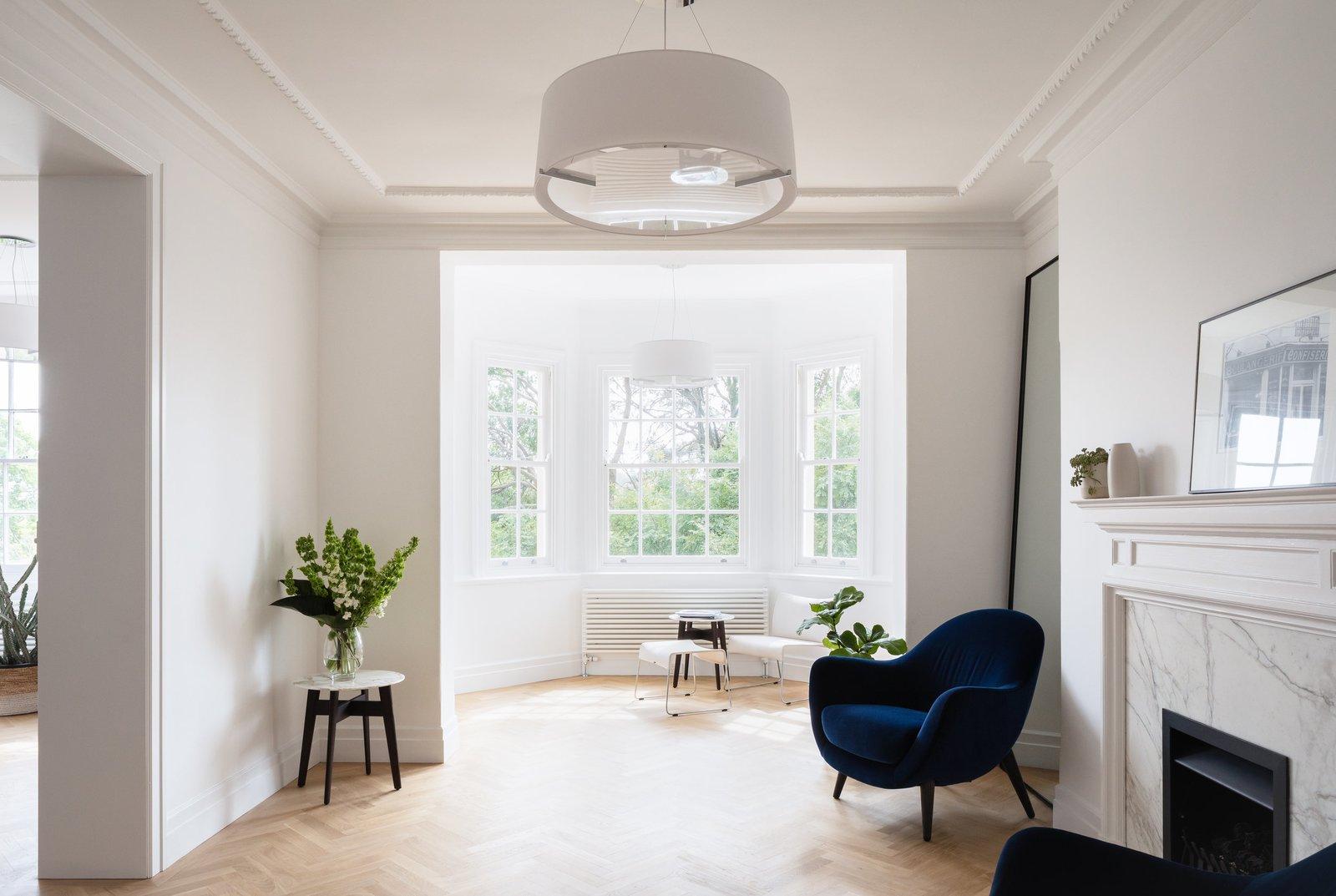 Living Room, Coffee Tables, Chair, Light Hardwood Floor, Pendant Lighting, and Wood Burning Fireplace Living room  K Apartment