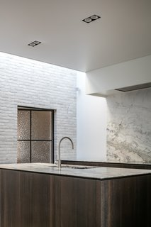 This minimalist Belgian kitchen extends its marble backsplash up the height of the wall to give the open space a greater feeling of enclosure.