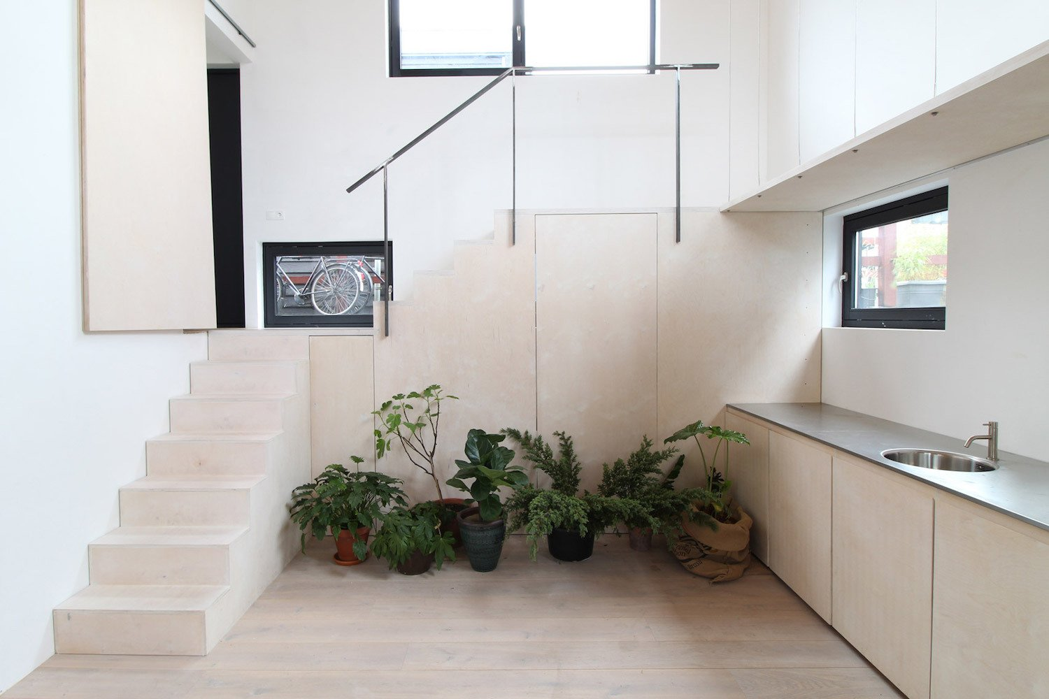 Tatami Home is a minimalist floating house located in Amsterdam, The Netherlands, designed by Julius Taminiau Architecten. The home is characterized by built-in storage and furniture in order to maximize the small space interior. The architect was inspired by traditional tatami rooms from Japan in order to guide the proportions of the internal layout. Tatami mats have similar proportions to plywood panels, which were used abundantly throughout the space. An open staircase serves as a partition separating the the living area from the dining room and kitchen.  Interiors