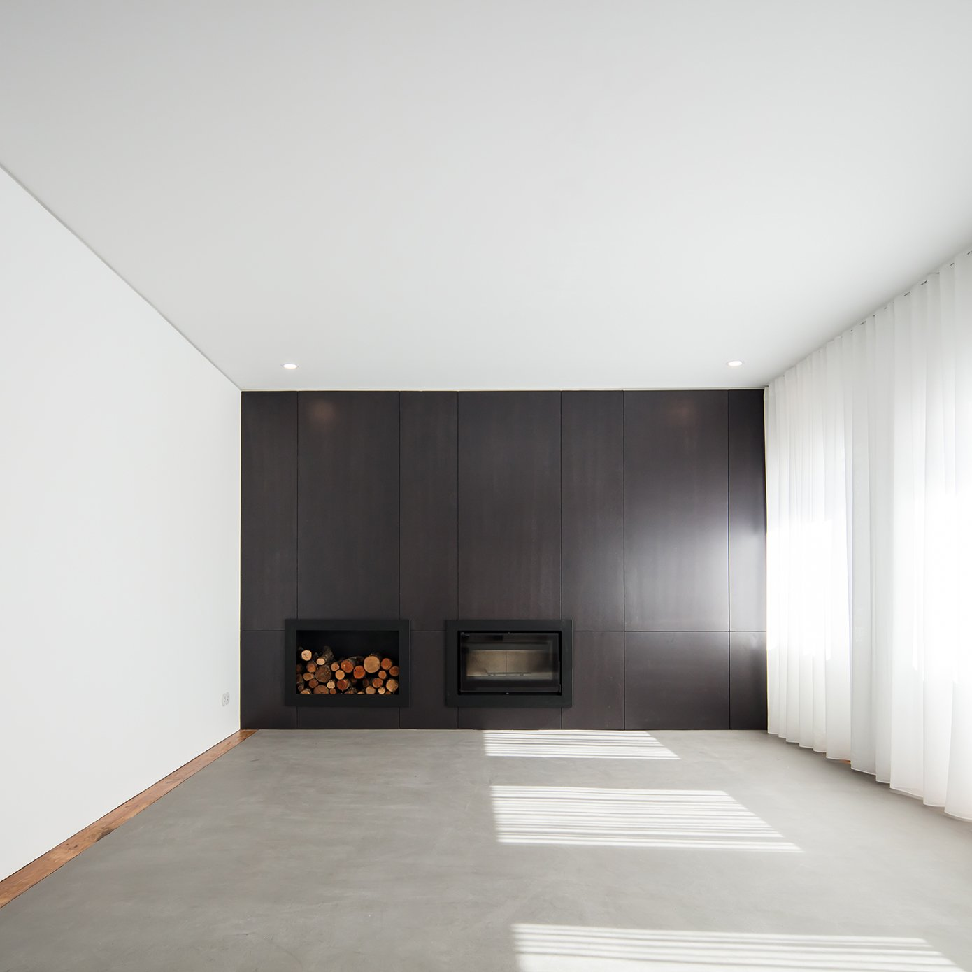 """Sao Francisco House is a minimalist residence located in Guarda, Portugal, designed by Filipe Pina. The project is an urban typical house of the first half of the 20th century, presenting three sides and a garden. The surrounding buildings are characterized by several types of construction, a consequence of the successive city urbanistic growth stages. The clients wanted a pragmatic solution to the project, """"willing to renew and rehabilitate the house with minimum demolition and in the most economical way"""". The optimal conditions and building characteristics of the house allowed for a good project development. Soon, the designers understood that the living spaces of the house needed to be simplified, as it did show some old-fashioned elements added over time by the different owners, with external parts losing their coherence and some gloomy interiors agglomerated in quite messy, obsolete and isolated rooms. They kept the original functional layout of the house, where we only inserted few changes in view of adapting it to actual modern requirements, namely for the kitchen, toilets and bathrooms, and very seldom demolitions which allowed new internal paths. It was also decided to keep the original floors, wooden structures, some the roof and surfaces. Now the house lives from its inside where all spaces merge into one unique light and bright room.  Interiors"""