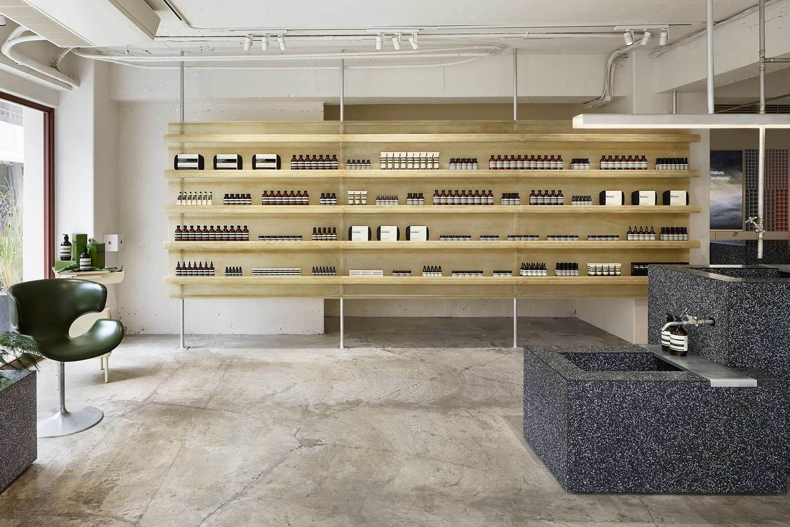Aesop Jiyugaoka is a minimalist Aesop store located in Tokyo, Japan, designed by ciguë. The space features a raw aesthetic, comprised mainly of concrete and the use of fiberglass laminated resin mounted on vibrated aluminum for the product display shelves. The resin not only has an earthy appearance, but is also semi-transparent as well. The fiberglass can be produced with curved features, thus the shelves and the structure itself are softly curved. The checkout and sink counters are constructed in terrazzo.  Interiors