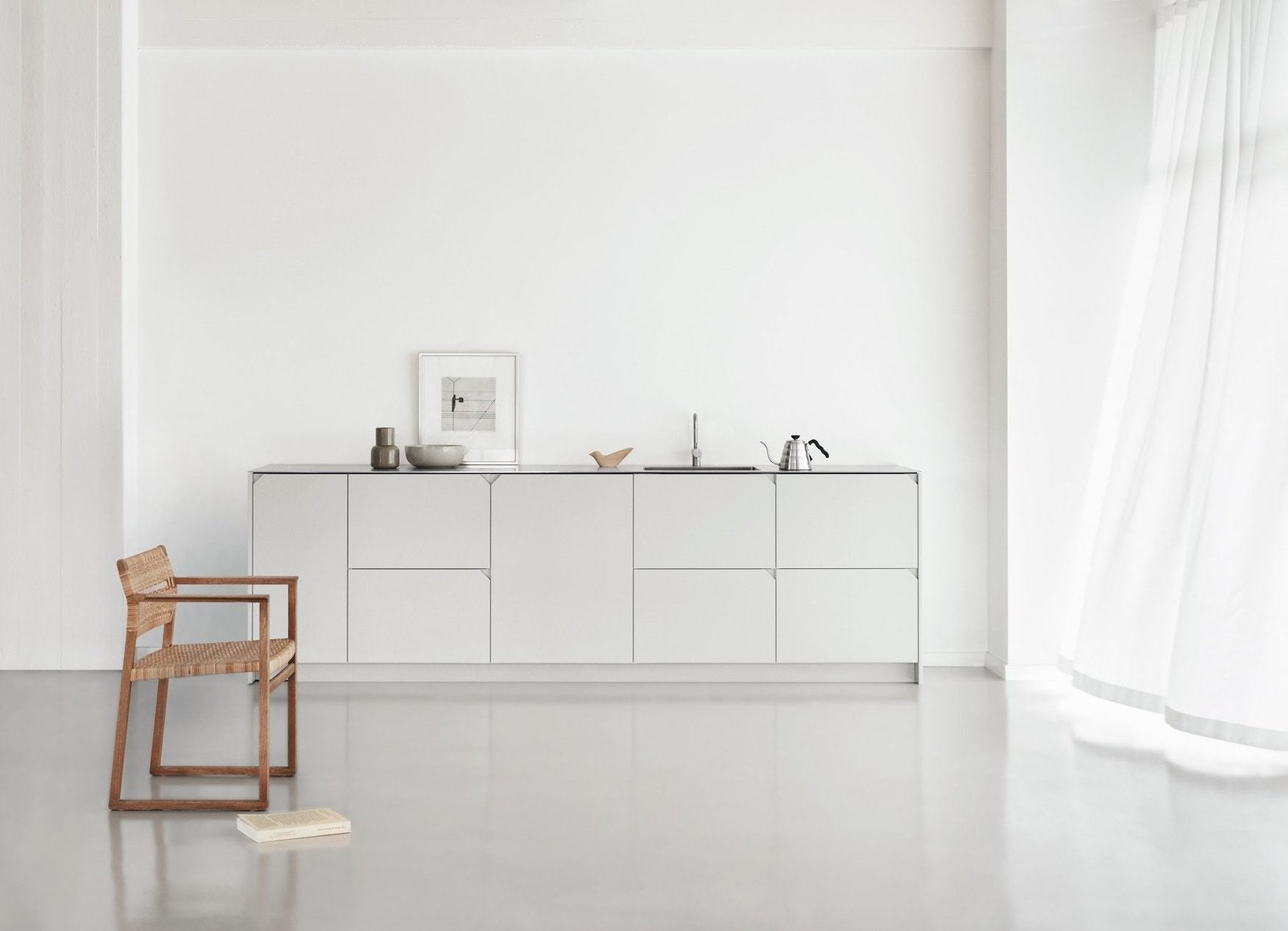 Degree is a minimalist kitchen system created by Copenhagen-based designer Cecilie Manz for Reform. Cecilie Manz has designed a kitchen based on simple principles; balancing functionality and a hospitable atmosphere. The steel countertop is a practical and raw expression that is balanced with warm shades of the cabinet fronts; the golden Oregon Pine and rich painted grey. The wood grain of the Oregon Pine is laid at a 45 degree angle, softly contrasting with the horizontal and vertical lines of the kitchen. The geometric notch handle is placed in the corner of each front and adds a graphic element to the kitchen. The simple details and honest materials create a classic but modern look. A comfortable backdrop for everyday life.  Interiors