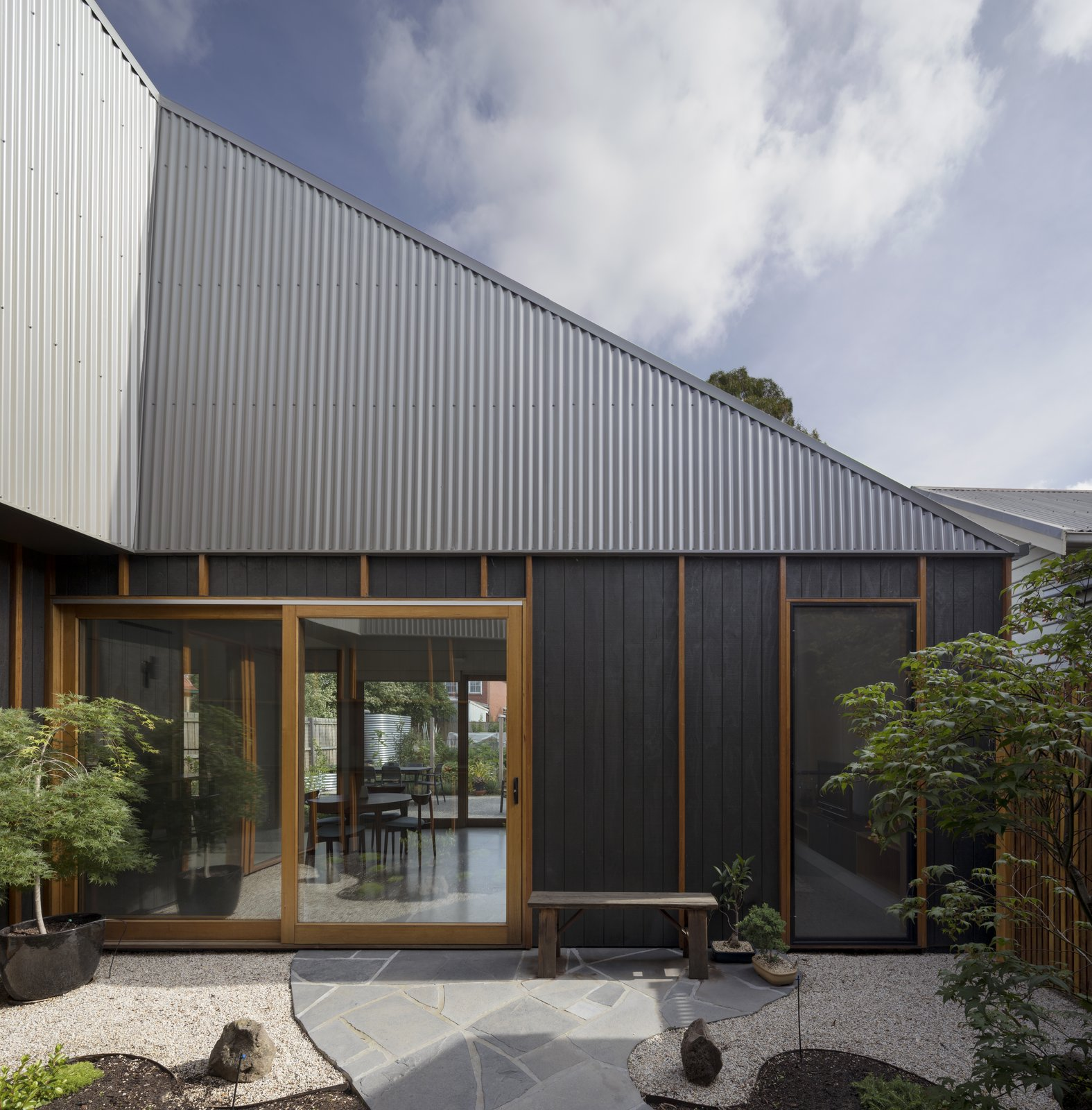 Outdoor, Garden, Hardscapes, Pavers Patio, Porch, Deck, and Gardens The owners, a couple in their 40s with a young child, wanted a home with easy access to a garden.  Photo 4 of 10 in A Family Home in Australia Features a Playful Version of the Classic Pitched Roof