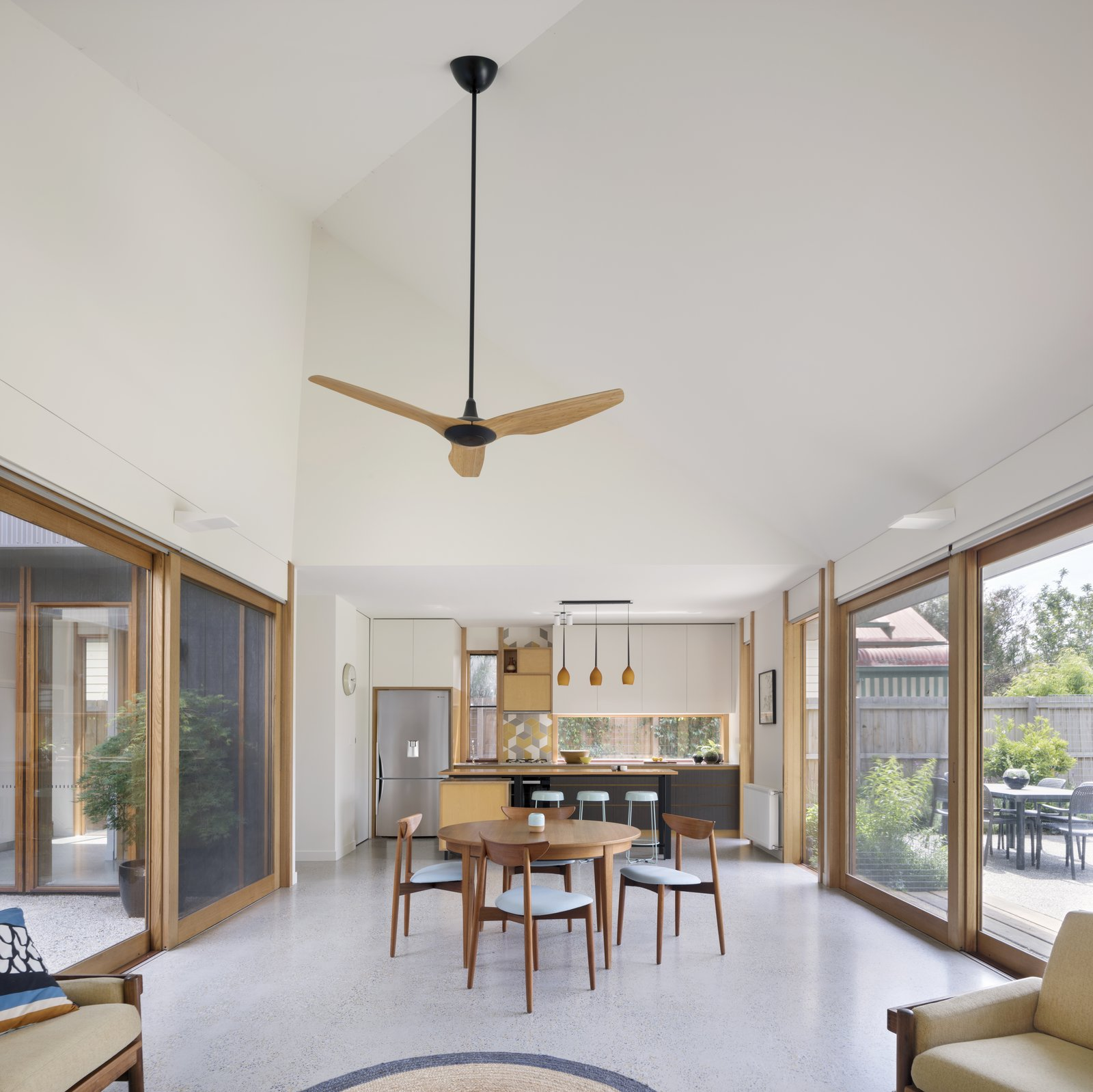 Dining Room, Chair, Table, Bar, Pendant Lighting, and Wall Lighting Blackbutt window treatments and a polished concrete floor unify the kitchen, dining, and living areas on one end of the courtyard. A Big-Ass Haiku ceiling fan can provide extra air.  Photo 5 of 10 in A Family Home in Australia Features a Playful Version of the Classic Pitched Roof
