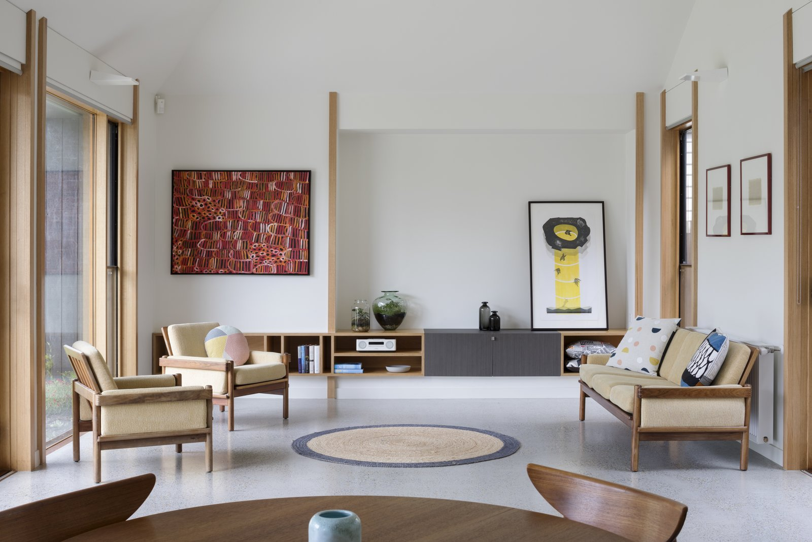 Living Room, Chair, Sofa, Wall Lighting, Concrete Floor, Rug Floor, Storage, and Shelves Plasterboard was used on the walls and ceilings of the interiors to accentuate an abundance of natural light.  Photo 7 of 10 in A Family Home in Australia Features a Playful Version of the Classic Pitched Roof