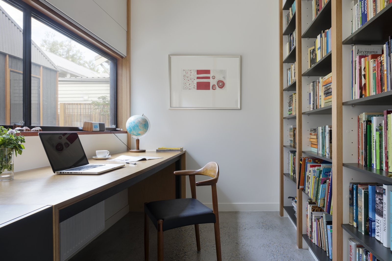 Office, Chair, Desk, Bookcase, and Concrete Floor One homeowner is studying part-time and requested a quiet workspace in the home. Her desk is made out of plywood and licorice linea from Laminex.  Photo 8 of 10 in A Family Home in Australia Features a Playful Version of the Classic Pitched Roof