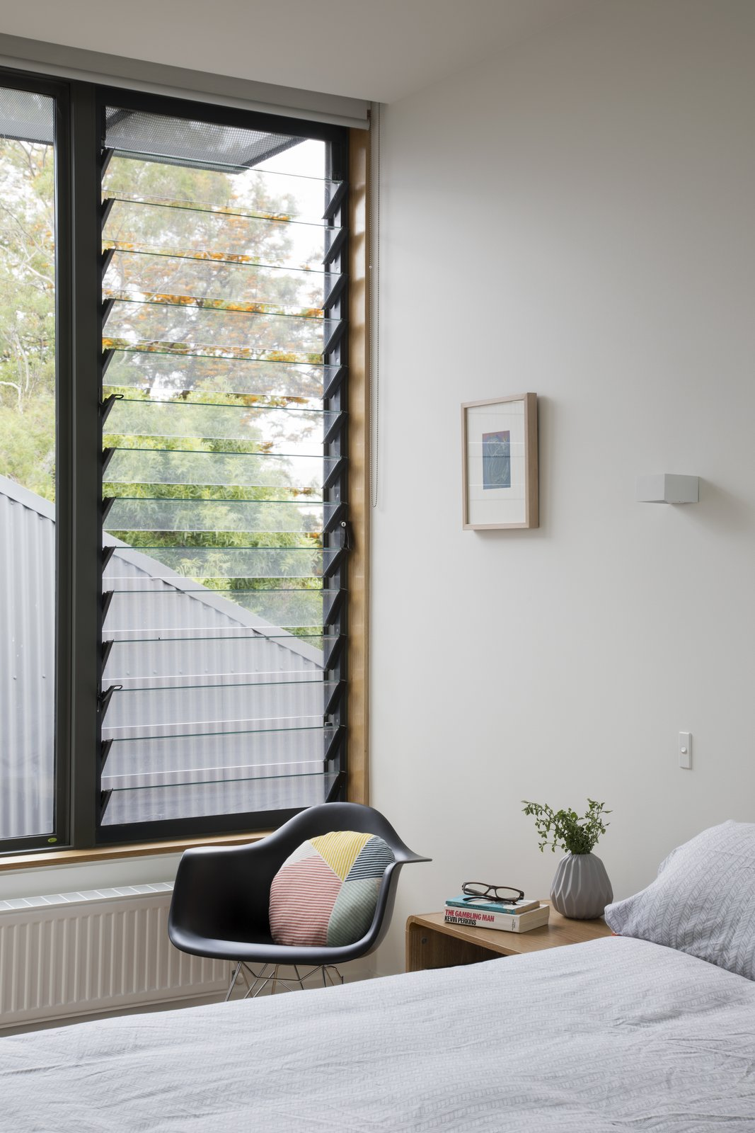 Bedroom, Bed, Night Stands, Wall Lighting, and Chair A Breezway Louve window brings air into a bedroom.  Photo 9 of 10 in A Family Home in Australia Features a Playful Version of the Classic Pitched Roof