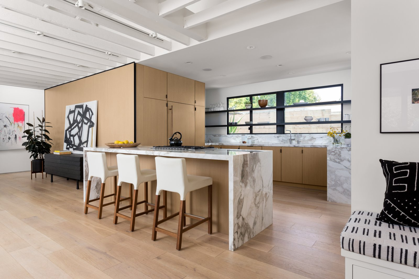 Kitchen, Range, Marble, Wood, Light Hardwood, Marble, Track, and Recessed Blu Dot stools line up against calacatta gold extra countertops. The custom cabinetry was outfitted by Semihandmade with Ikea cabinet bodies.  Best Kitchen Track Marble Photos from The Woman Who Grew Up in This L.A. Home Returned to Give it a Stunning Renovation