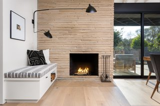 The original fireplace was resurfaced using Colorado Buff Ledge stone, which offsets the black-and-white shades of the custom bench and Stilnovo sconce.