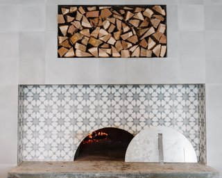 The six-foot wood burning oven features the same sunburst tile from the floors.