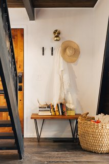 Four hooks and a bench, both from CB2, create a small, dedicated entryway next to the front door.