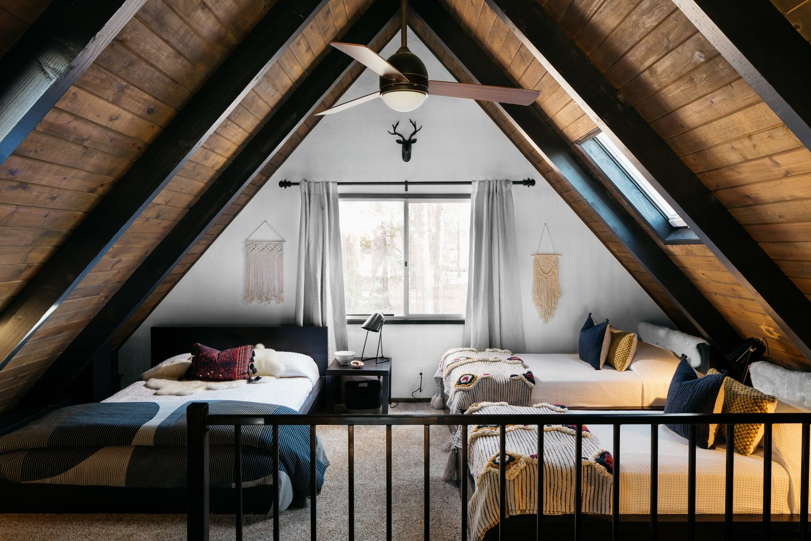 """Bedroom, Bed, Night Stands, Ceiling, and Carpet """"We wanted to create a bohemian feel in the bedroom and the loft spaces,  Bedroom Carpet Ceiling Night Stands Photos from A 1970s A-Frame Cabin in Big Bear Is Brought Back to Life"""