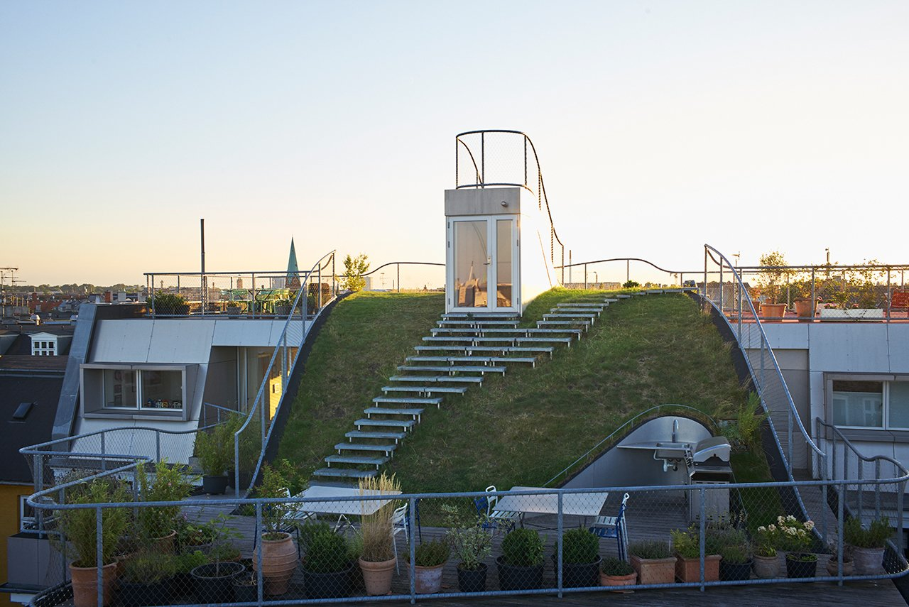 Outdoor, Walkways, Decking Patio, Porch, Deck, Rooftop, Grass, Hardscapes, and Metal Fences, Wall Since the open space is owned by everyone in the building, De Smedt wanted it to feel that way.  Photo 1 of 5 in This Copenhagen Rooftop Renovation Embodies the Future of Urban Design