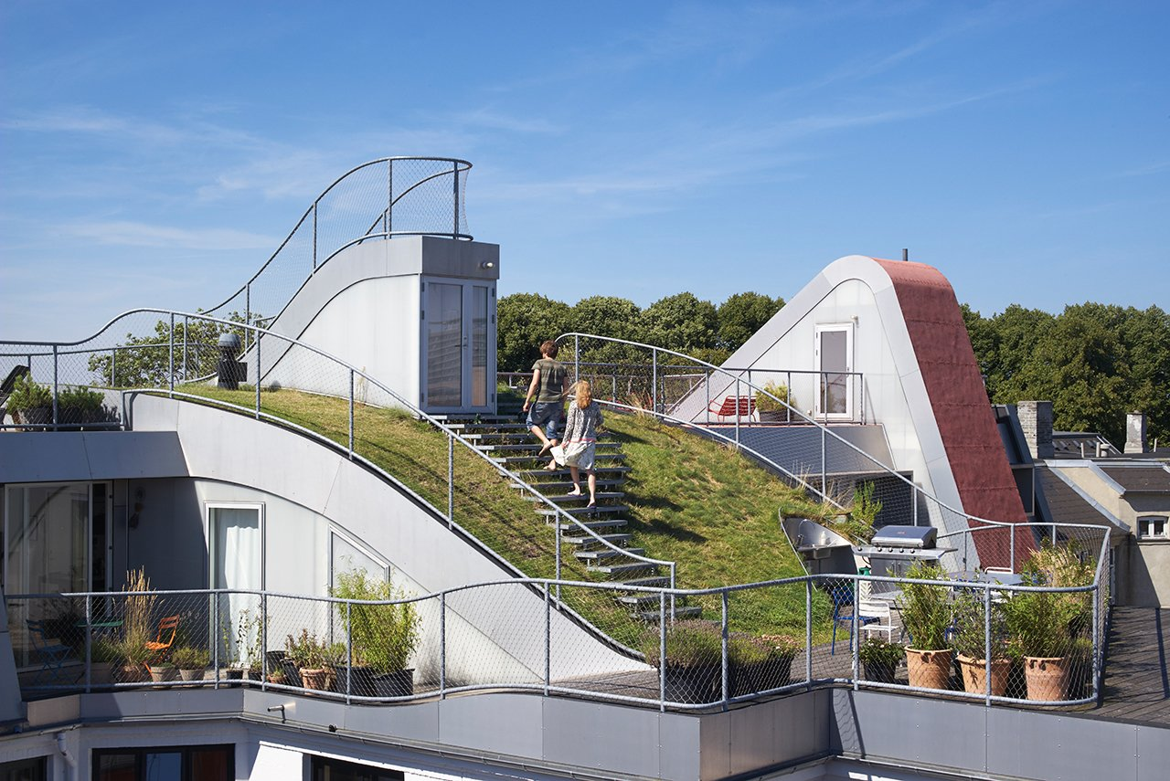 Outdoor, Metal, Rooftop, Hardscapes, Wood, Decking, Grass, and Walkways The construction was done to make sure that the four areas of the roof — the sundeck, grass hill, play space, and outdoor terrace — all felt like distinct but united areas.  Best Outdoor Grass Metal Photos from This Copenhagen Rooftop Renovation Embodies the Future of Urban Design