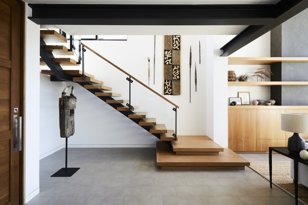 The staircase was moved to be more prominently featured in the home's renovation. The owners' surrounding art collection makes it even more striking.