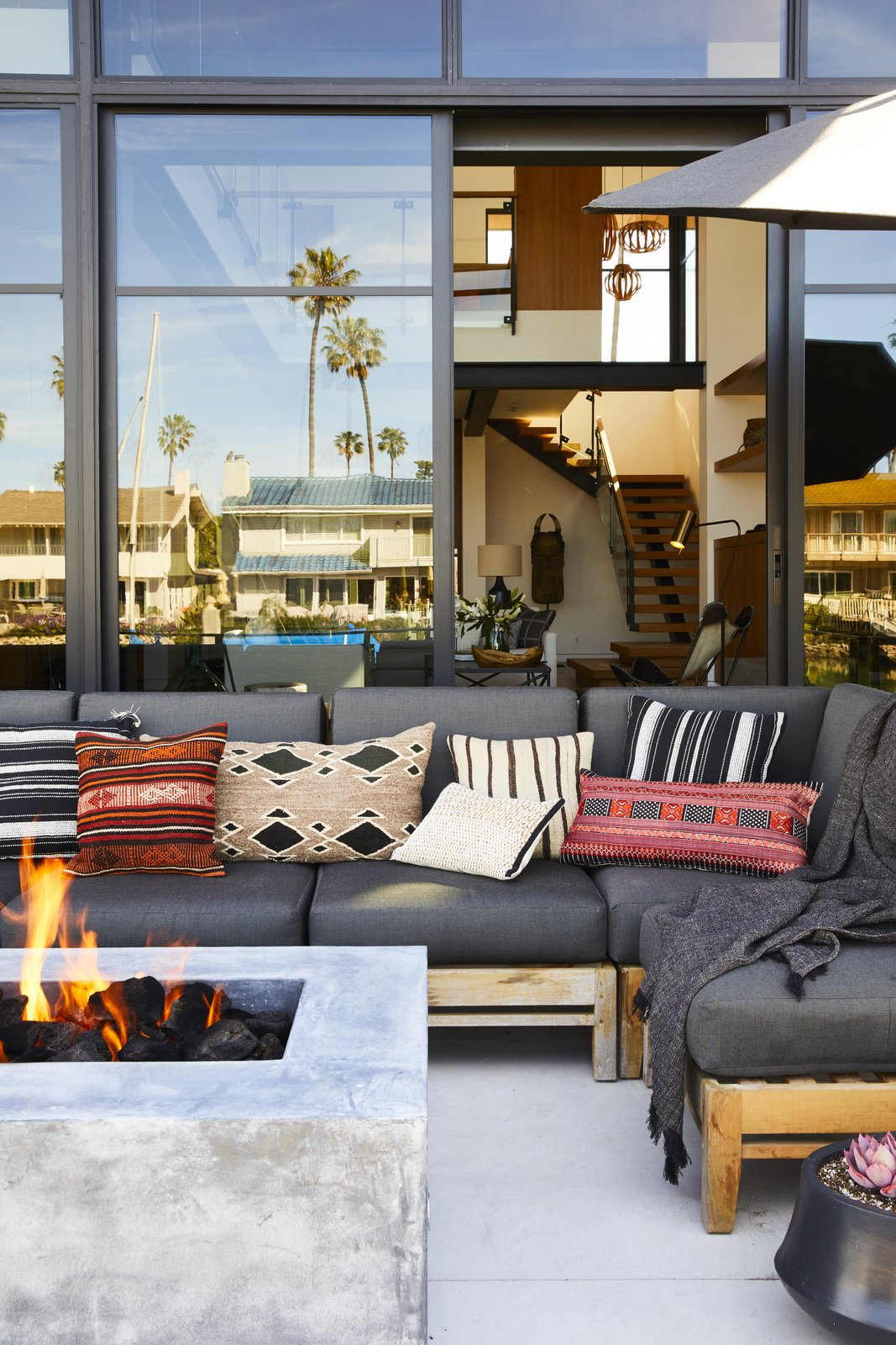 """Outdoor, Back Yard, Concrete Patio, Porch, Deck, and Planters Patio, Porch, Deck """"The home is special because it feels curated, but very personal,  Photo 4 of 19 in 18 Modern Fireplaces and Fire Pits to Inspire Outdoor Living from This Renovation Will Make You Rethink the Typical Look of a California Beach House"""