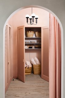 """""""The dramatically tall and wide arched entranceway with the modernized Louver closet doors reminds me of a 1930s Hollywood film set,"""" Hesser says. The closets are used to store props for events and shoots, including lots of wine."""
