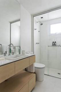 The main bathroom is unified with the rest of the home thanks to the same burnt cement flooring. A solid wood countertop was installed by Inovart Woodworking, and the adjoining white quartz countertop was picked from MSA Marmoraria.
