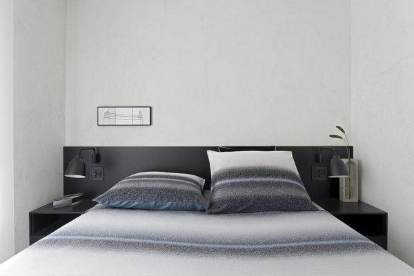 The black lacquer finish used in the common area was repeated in a headboard for the master bedroom.