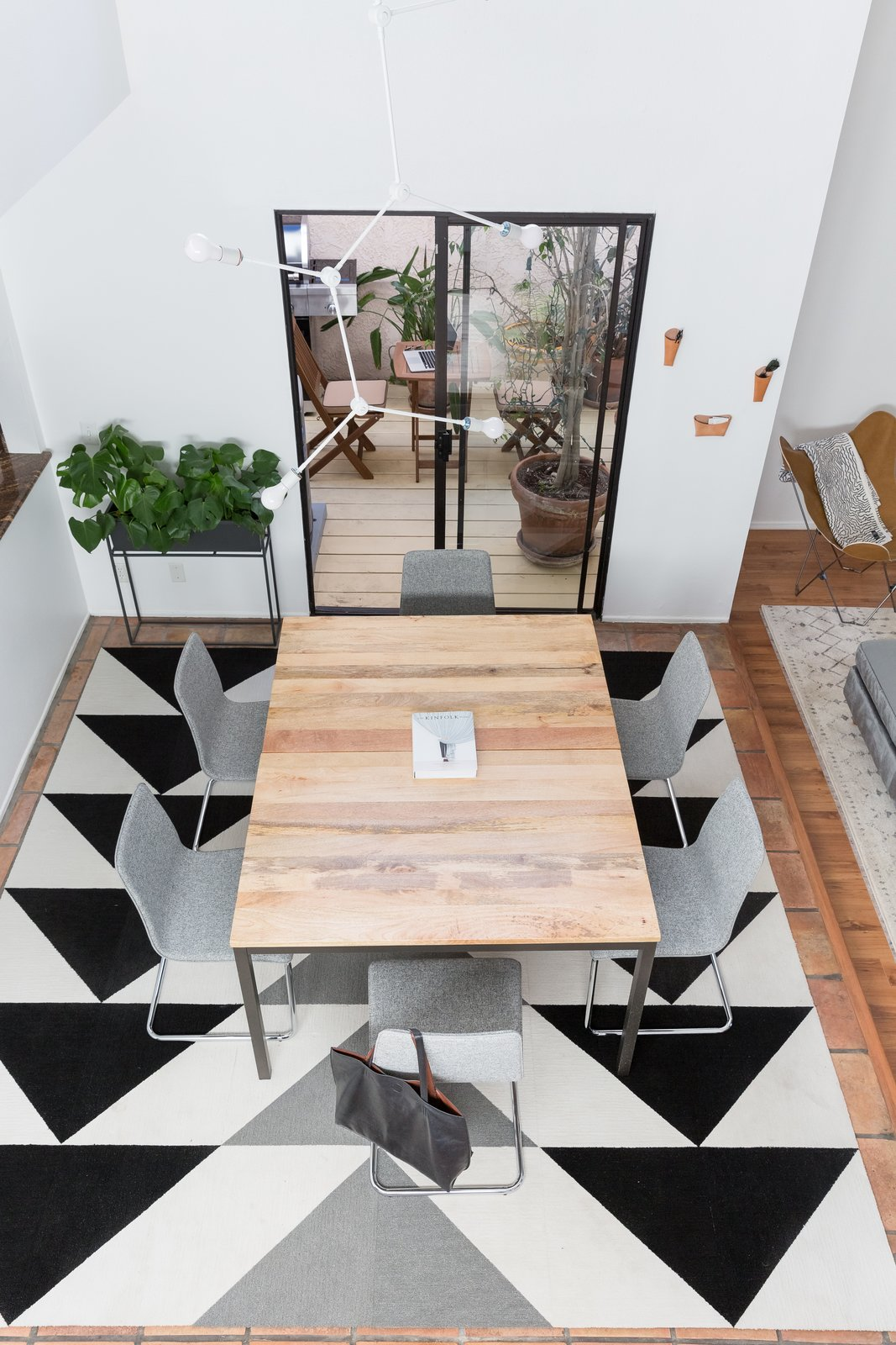 Dining, Ceramic Tile, Table, Chair, Rug, Pendant, and Medium Hardwood Geometric patterns were a big part of the home's design, and that's best showcased by the dining room's  Best Dining Medium Hardwood Table Ceramic Tile Photos from A Venice Beach Abode Becomes a Chic Co-Living Space Where Everything's For Sale