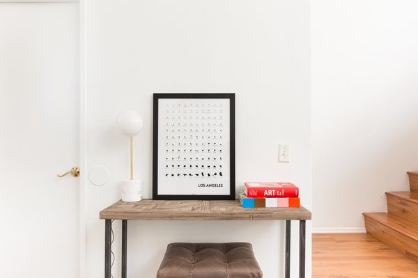 The entryway is minimal yet stylish, thanks to simple and location-specific artwork and a couple of brightly covered books.