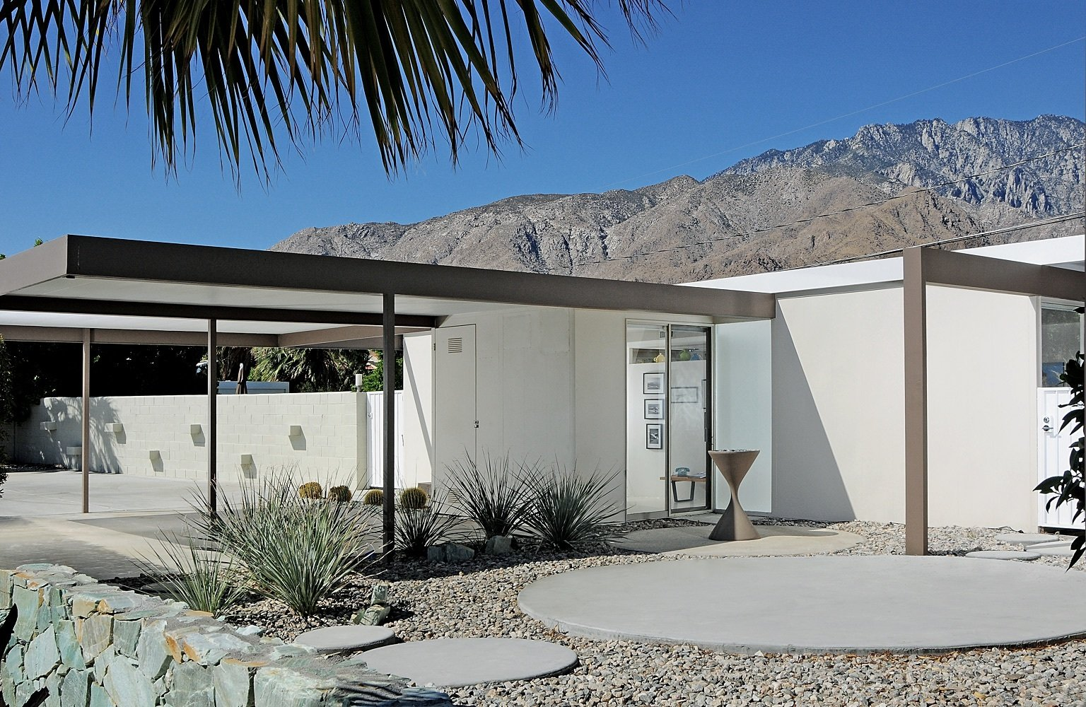 Exterior, Metal Roof Material, Flat RoofLine, Metal Siding Material, Glass Siding Material, House Building Type, Concrete Siding Material, and Mid-Century Building Type The two-bedroom, two-bathroom house has a pool and an open air carport on a fourth-acre lot.  Photo 3 of 6 in You Can Now Buy One of Palm Springs's Most Historic Homes For $839K