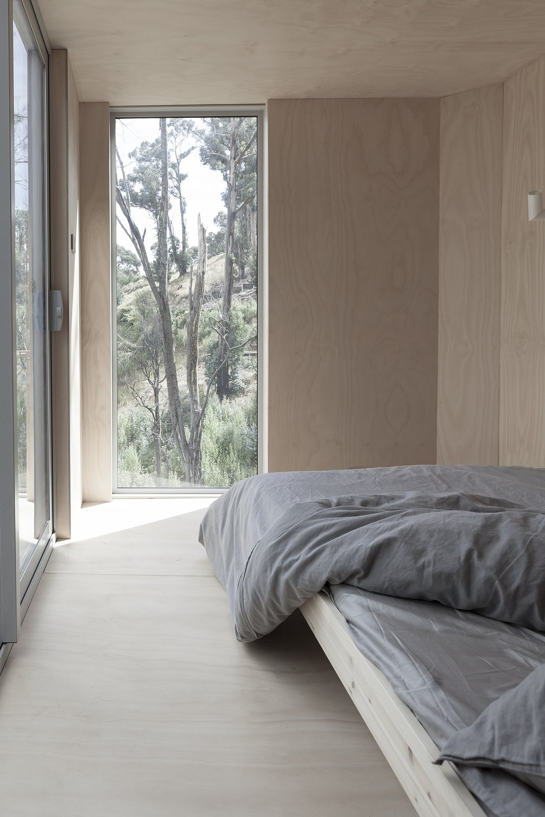 Bedroom, Bed, Plywood Floor, and Wall Lighting Since artwork was passed over for the beauty of the outdoors, windows create light and movement in the two bedrooms.  Photo 6 of 8 in This Off-Grid Container Home in Australia Disappears in Nature