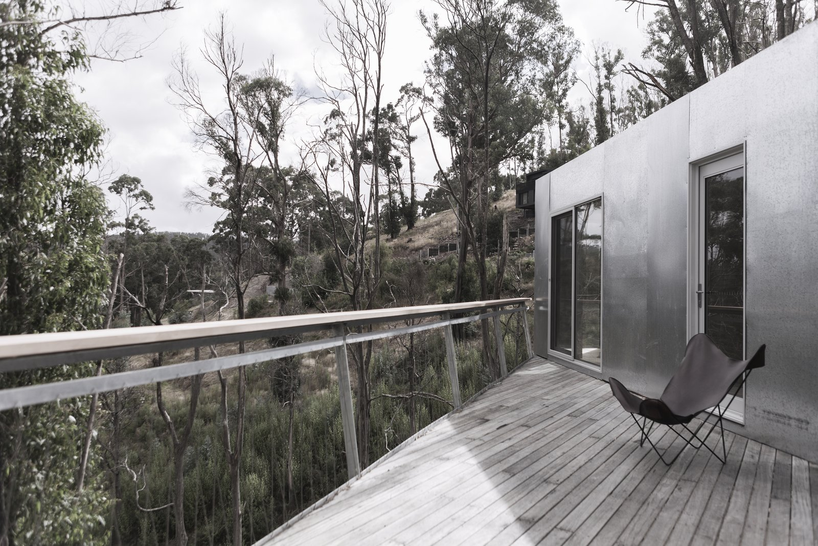 Exterior, Flat RoofLine, Metal Siding Material, Shipping Container Building Type, Green Roof Material, and House Building Type A deck on the southside of the home is the perfect place to take in the ocean view.  Photo 7 of 8 in This Off-Grid Container Home in Australia Disappears in Nature