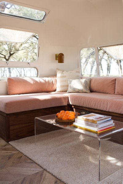 Storage under the blush-toned sofa makes it easy to keep the area neat. A CB2 coffee table sits above a Dash & Albert rug, and the sconces were sourced from Schoolhouse Electric. Kaindl flooring and Benjamin Moore's