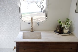 A detachable shower head in the bathroom makes dog washing easier, and a composting toilet allows the owners to go off-the-grid for longer periods of time. Aside from that, walnut and marble accents — plus the same Corian Dune prima deep sink used in the kitchen — make the bathroom pretty, too. The shower tiles were found at Lowe's.