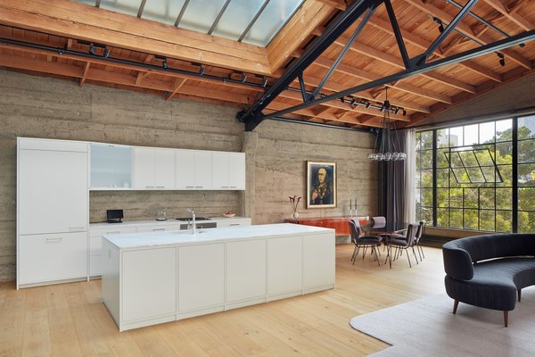 Kitchen, Drop In Sink, White Cabinet, Range, Refrigerator, Pendant Lighting, Rug Floor, Wall Oven, Track Lighting, and Light Hardwood Floor This loft was once a knitting mill in San Francisco.  Photo 9 of 10 in Top 10 Cities to Witness Stunning Architecture Across America