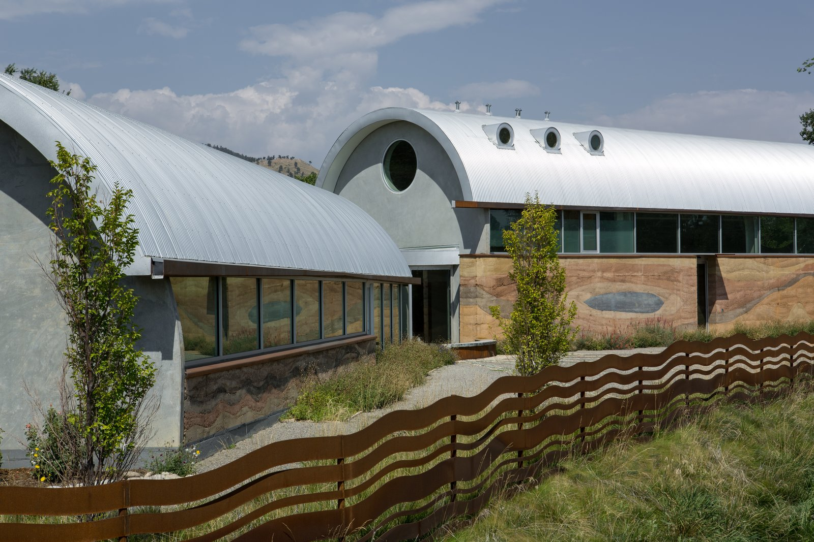 Exterior, Curved RoofLine, Metal Roof Material, and Wood Siding Material The circle, a classic artistic and symbolic figure, can be spotted throughout the property.  Photo 5 of 6 in Two Rammed-Earth Buildings Host a Sustainable Live/Work Space For a Colorado Artist