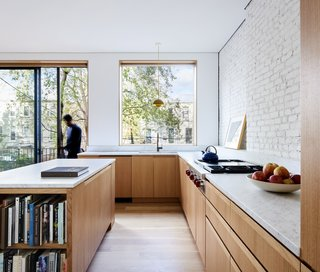 American white oak was used for the flooring throughout the house, including the sun-filled kitchen. A Brendan Ravenhill hangs above the sink, and a Wolf cooktop was installed opposite the island.