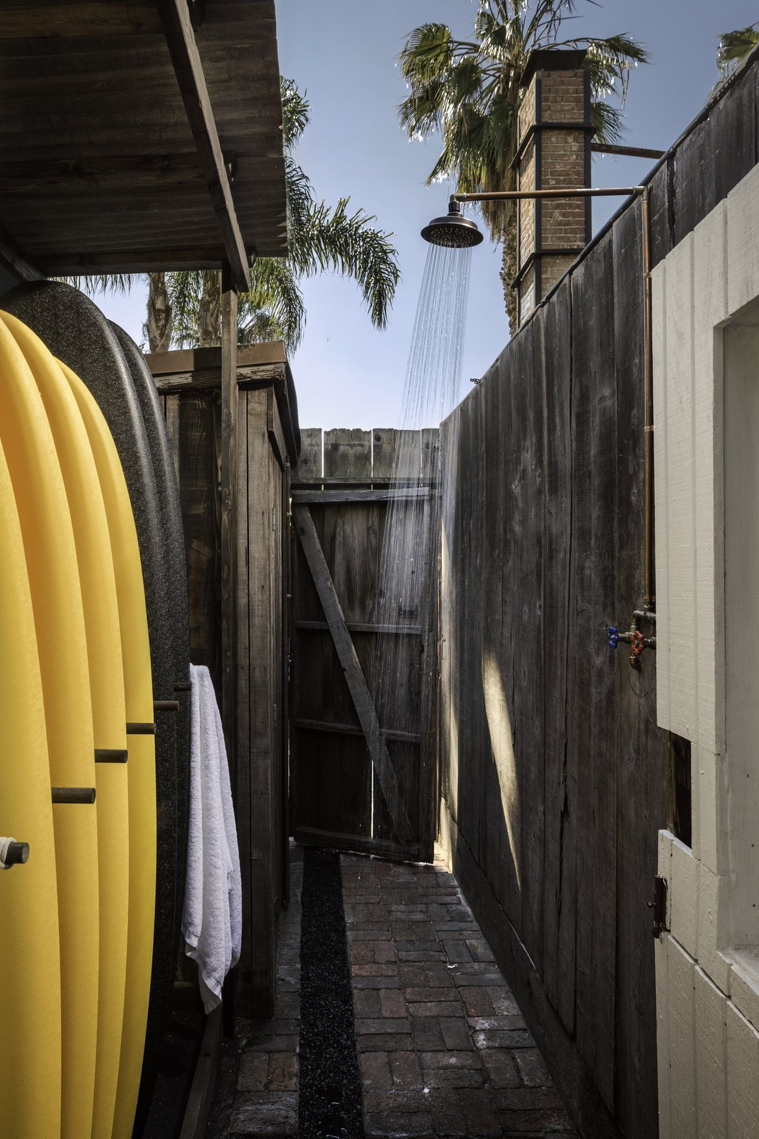 """Outdoor, Side Yard, Wood Fences, Wall, Shower Pools, Tubs, Shower, and Walkways  """"I want the members to feel completely comfortable and not want to leave,"""" she says. """"The property still maintains a beach-house charm.""""    Photos from A 1940s Beach Home Is Restored Into a Gorgeous Clubhouse in L.A."""