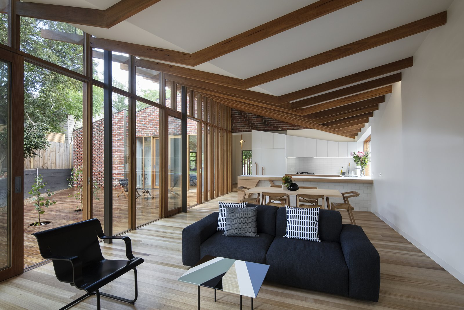 """Living Room, Chair, Sofa, Coffee Tables, and Medium Hardwood Floor """"The beams fold and taper back to the original roof line, which means each beam is unique, just like in nature,"""" Dunin says.     Photo 6 of 8 in A Backyard Eucalyptus Becomes the Muse For This Home Remodel"""