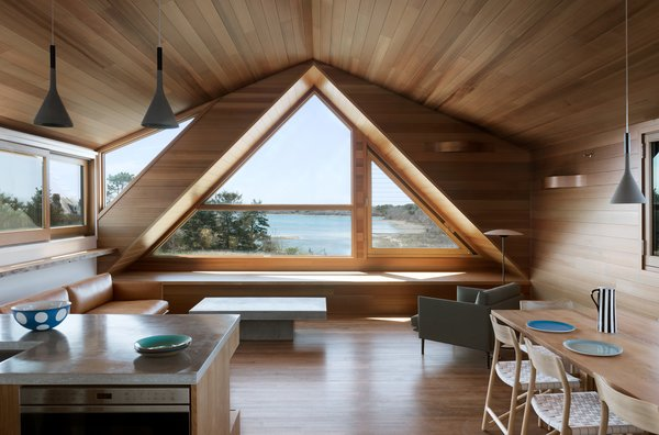 """""""Because the living room occupies the gable, the resultant space is triangular in feel,"""" Thompson says. So she heightened that look with an oversized triangle window, which maximizes views of the cove. Western red cedar was chosen for the walls, and three-inch red oak was chosen for the interior floors. The windows are encased in Alaskan Yellow Cedar."""