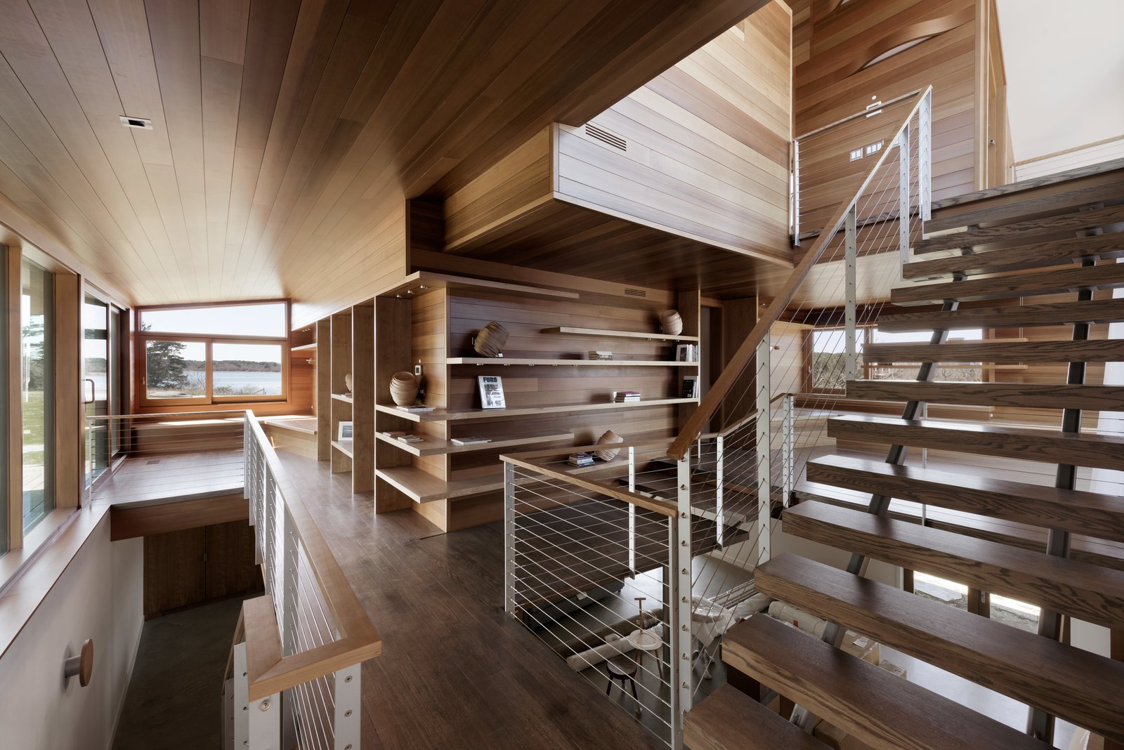 """Staircase, Metal, Wood, and Wood Thompson wanted to create """"layered and veiled spaces"""" inside, which was achieved with multiple places to gather in the main corridor. The corridor is open from the second floor down to the basement, and has a combination of skylights and windows for ample light. Paradis MetalWorks supplied the rail and stair stringers.     Best Staircase Metal Wood Photos from A Saltbox Home Is Revamped to Embrace its Sublime Cove Setting"""