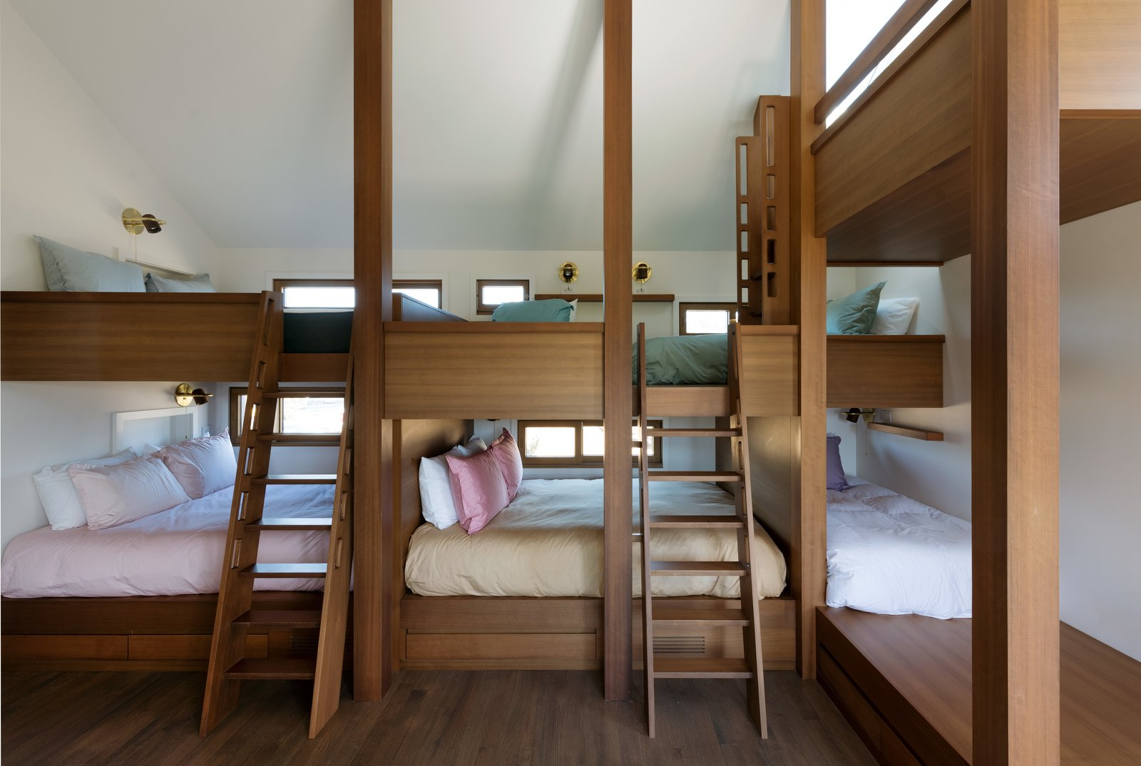 """Bedroom and Medium Hardwood Floor """"The two queen bedrooms can handle two couples, while the bunk-bed room can handle all the kids,"""" Thompson says. She also made sure every bunk had a window, to act as a """"mini room.""""    Photo 5 of 6 in A Saltbox Home Is Revamped to Embrace its Sublime Cove Setting"""