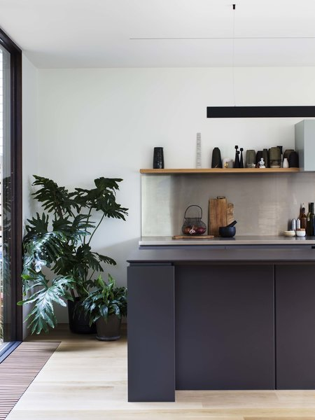 The minimalist kitchen is in keeping with the rest of the home: It has clean lines, few details, and that same classic contrast between black and white. The custom joinery is by Orana with fixtures by Roger Seller. The countertops are made of custom-cut Limestone.