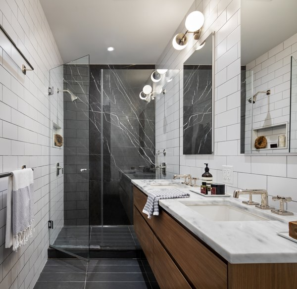 Barker mixed inexpensive subway tiles with an expensive marble slab in the master bathroom. The mix of high and low pieces defines the style of this home.