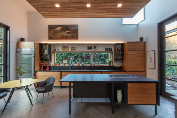 The open kitchen was converted from the original garage, and carries the wood pattern from the exterior inside with the accented ceiling.