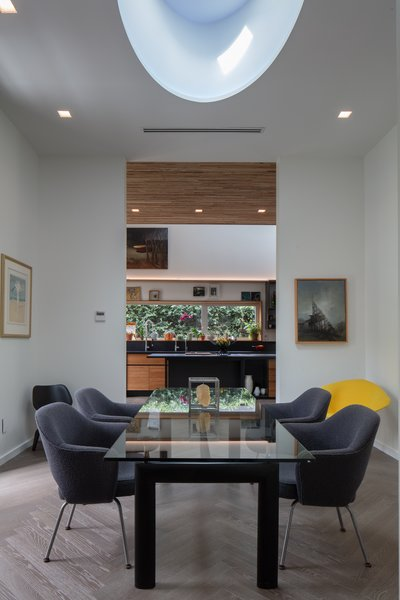 """""""Although the kitchen and dining room have distinct volumes, they are essentially connected to each other though the use of a full opening that shares the same ceiling height,"""" he notes."""