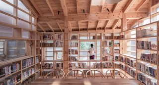 Inside, pinewood bookshelves surround a reading area without obstructing natural light.