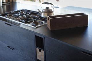 "This built-in storage finds use for the otherwise ""dead"" spaces around the appliances. A Gaggenau Vario 200 Series Gas Cooktop and a Water Kettle by Sori Yanagi are nearby."