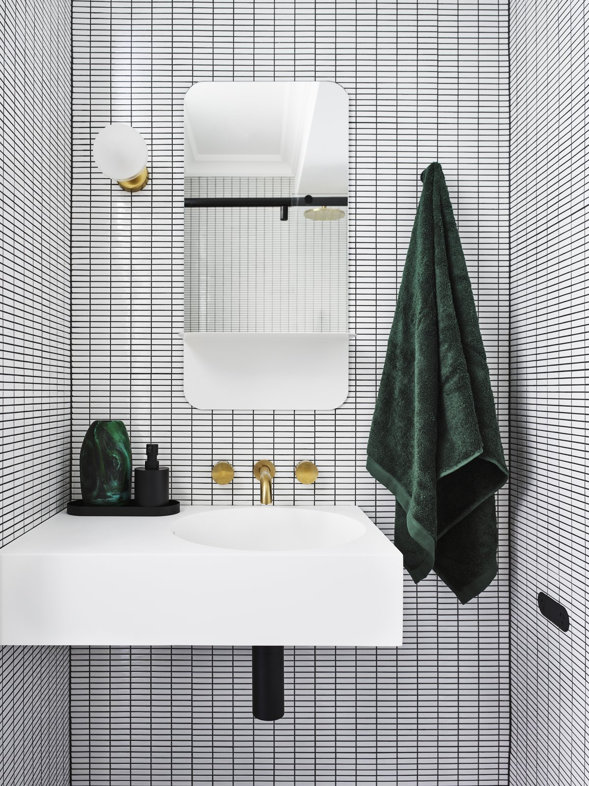 """If Bradley had to choose a favorite bathroom design in her portfolio, it would be this guest bathroom. """"Incorporating a strong, geometric pattern through the use of white, rectangular mosaic tiles with black grout created the illusion of space,"""" she says.  Photo 1 of 7 in How to Make Your Powder Room Look Absolutely Dynamite, According to the Experts"""