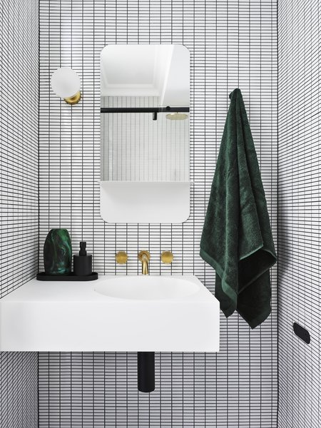 "If Bradley had to choose a favorite bathroom design in her portfolio, it would be this guest bathroom. ""Incorporating a strong, geometric pattern through the use of white, rectangular mosaic tiles with black grout created the illusion of space,"" she says."