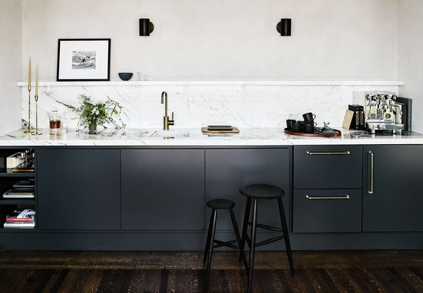 Matte black cabinetry balances out the shiny fixtures and marble countertops in this low-key kitchen.