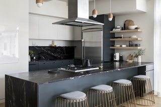 Existing Thermador appliances were used in the kitchen, alongside a dark granite stone that Nye found for the countertops. Bride's Veil by Phase Design stools sit under Terho by Mater pendant lights.